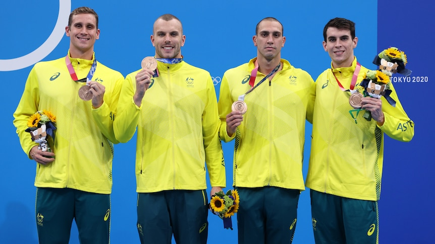 Four men in green and gold tracksuits hold bronze medals