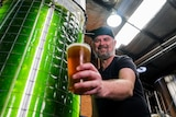 a man smiling and holding a beer next to a large vat with glowing green liquid