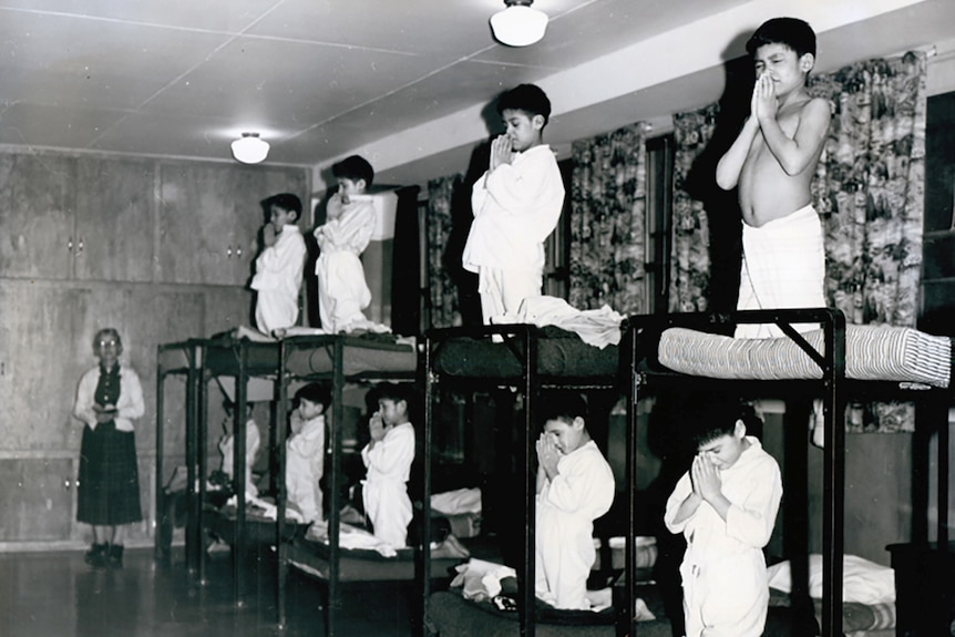A group of young boys kneels in prayers on bunk beds