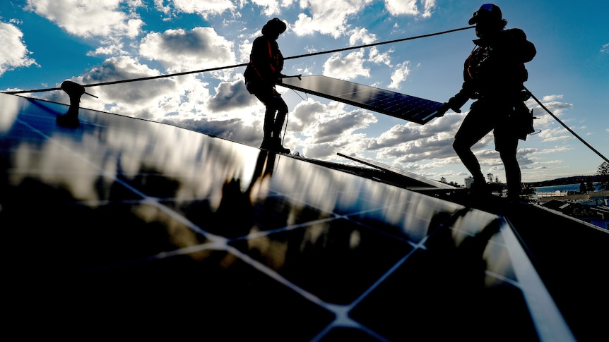 Silhouettes of two workers carrying a solar panel on a rooftop