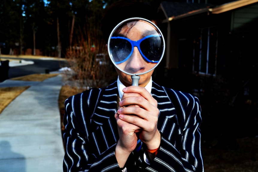 A person holds a magnifying glass to depict techniques to help you overcome imposter syndrome.
