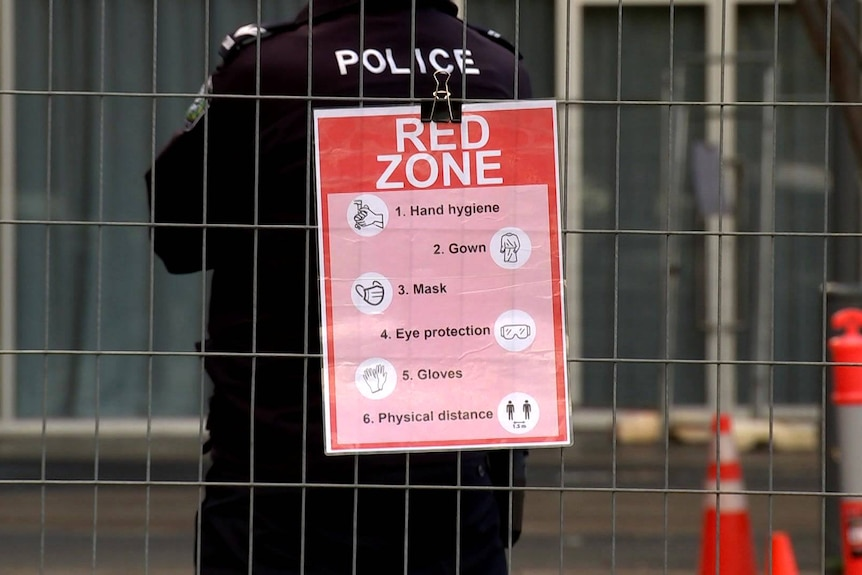 An SA Police officer stands next to a coronavirus warning sign outside the Pullman Adelaide.