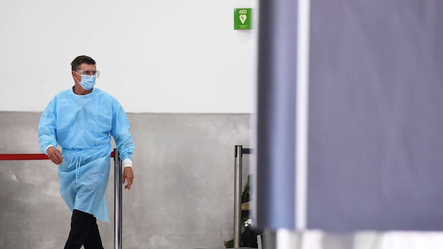 A man in blue PPE walks past a baggage carousel at an airport.