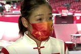 Liu Shiwen wearing a mask and with visible tears in her eyes at an Olympic venue.