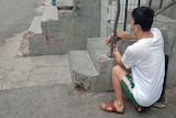 A person squats in place after being handcuffed to a rail beside a building in Urumqi.
