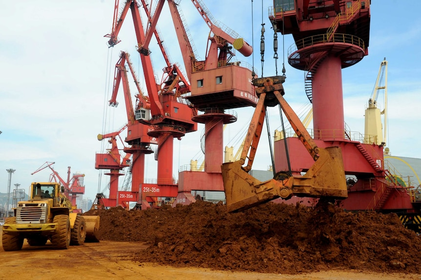 Iron ores are unloaded at a port in Lianyungang,