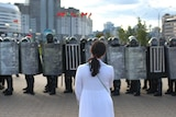 A woman in a white dress stands confronting a row of police with riot shields