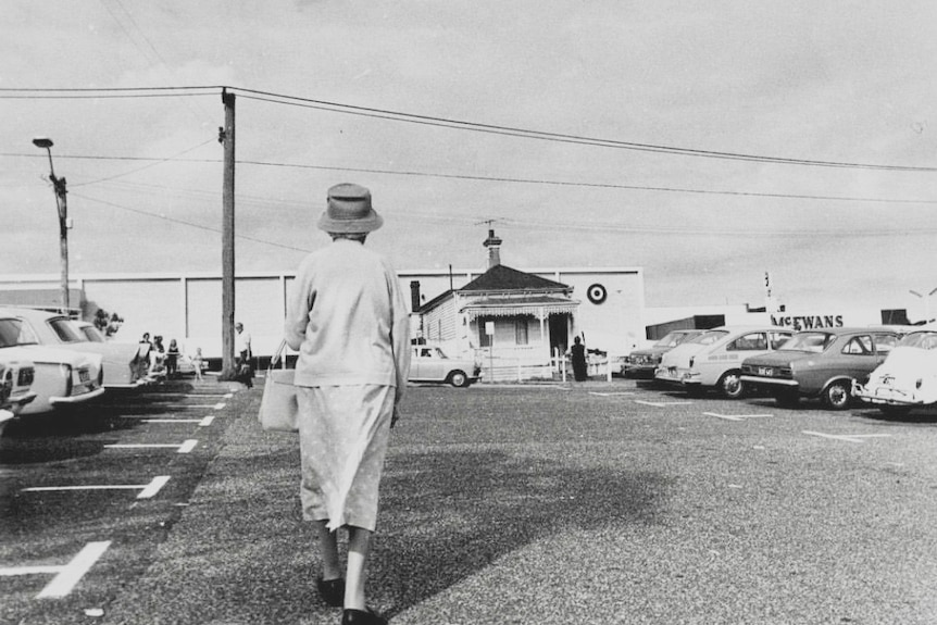 A black-and-white photograph of a woman walking across a carpark towards a small house in the middle of it all.