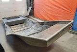 An aluminium boat, bent upwards in the middle, sitting on a concrete floor.
