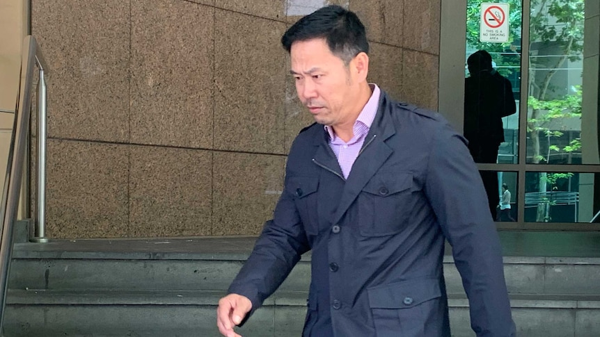 A man with black hair wearing a dark blue jacket and light coloured pants walks down the steps outside court.