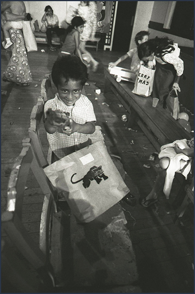 A small boy looks at the camera with a present.