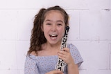 A young girl smiling while holding an oboe