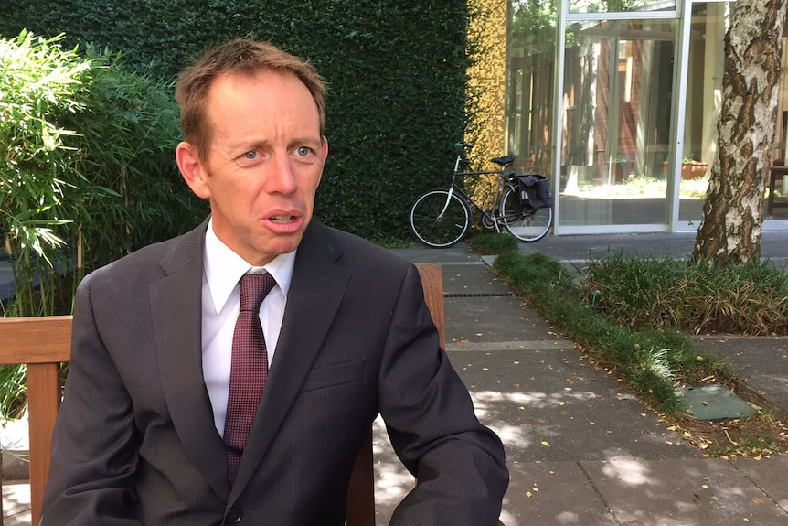 Shane Rattenbury with a bicycle in the background.