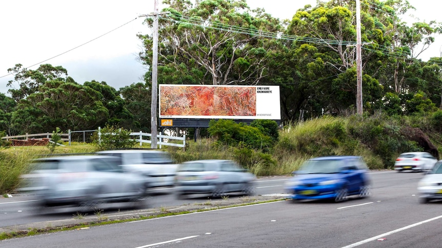 A billboard features a piece of art by a female artist on the side of a road as cars drive by.