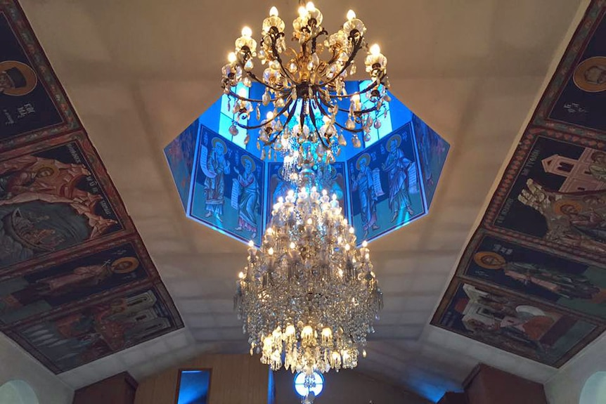 A large, glass chandelier hanging under a blue dome