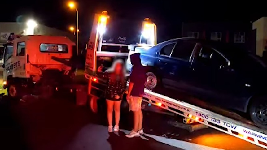 Two young people pose for a photo in front of a car that is loaded onto a tow truck