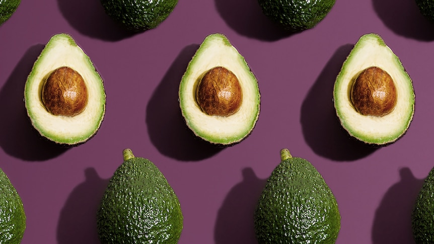Halved avocados on a purple background, in a story about how to choose, store and eat Hass and Shepard avocados