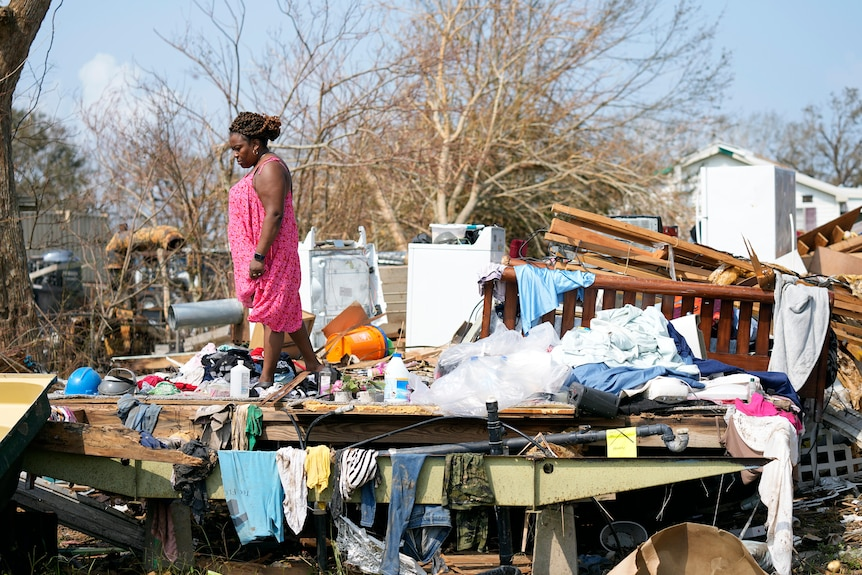 A woman inspects the wreckage of her home after Hurricane Ida