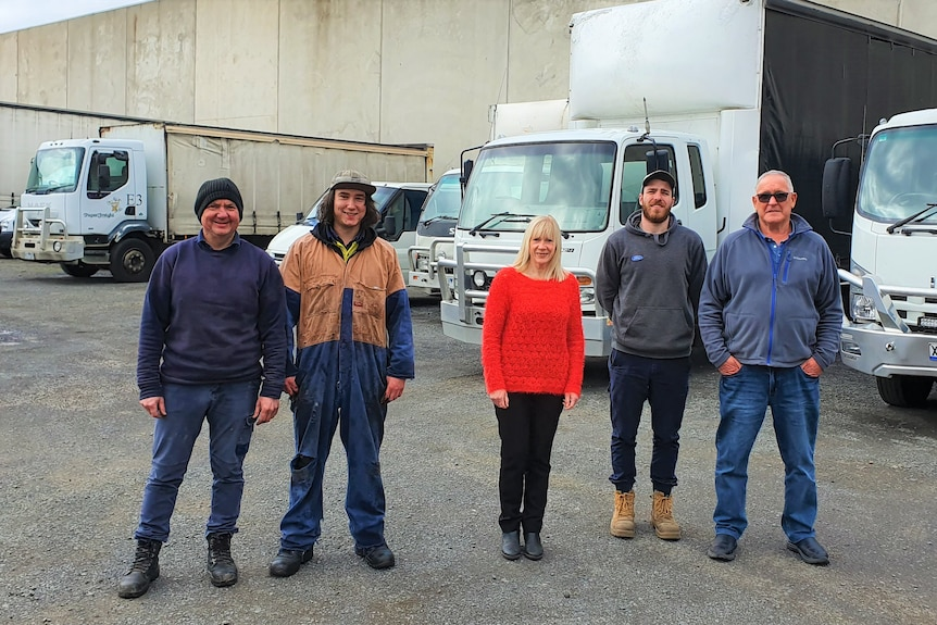 Four men and a woman stand in front of a row of trucks. They are wearing work clothes and boots, expect for a the woman in the m