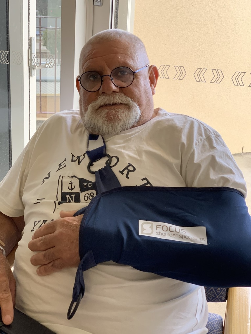 Robert Muir, his arm in a sling, sits in a chair in hospital after shoulder surgery.