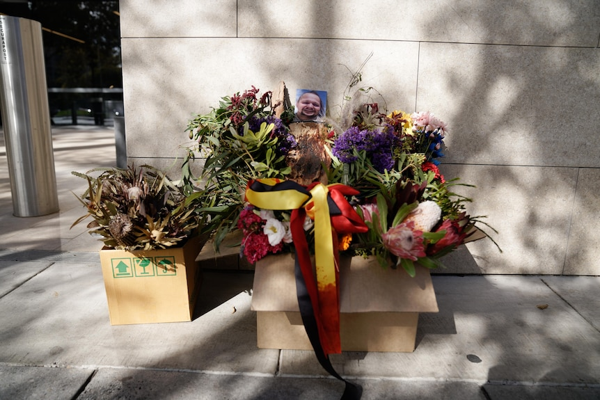 Flowers in a box with a photo of Wayne Morrison