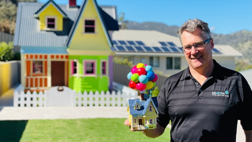 A man stands in front of a massive cubby house, holding a toy of the Pixar home that inspired it.