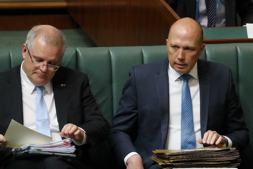 Two white men wearing blue ties and suits sit on a green bench.
