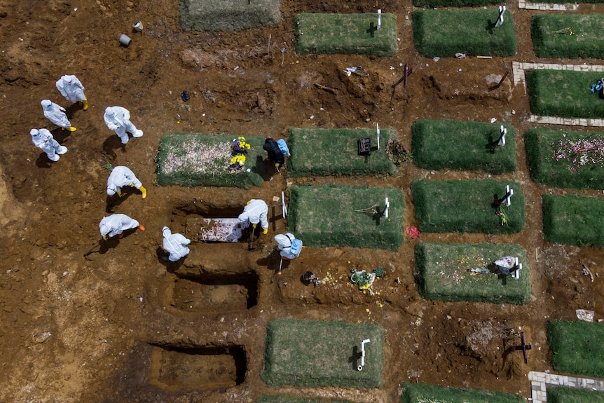 In an aerial view, workers bury a coffin containing the body of a COVID-19 victim
