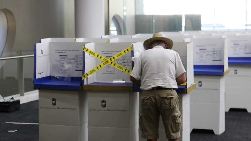 An older man wearing a short sleeve shirt, shorts and a wide brim hat, stands at a polling booth inside a room.