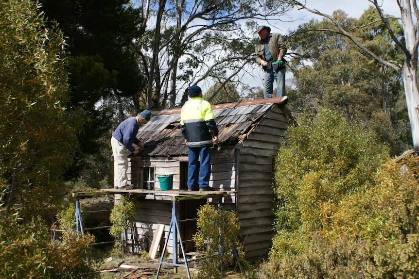 Volunteers reroofing one of Tasmania's iconic mountain huts.