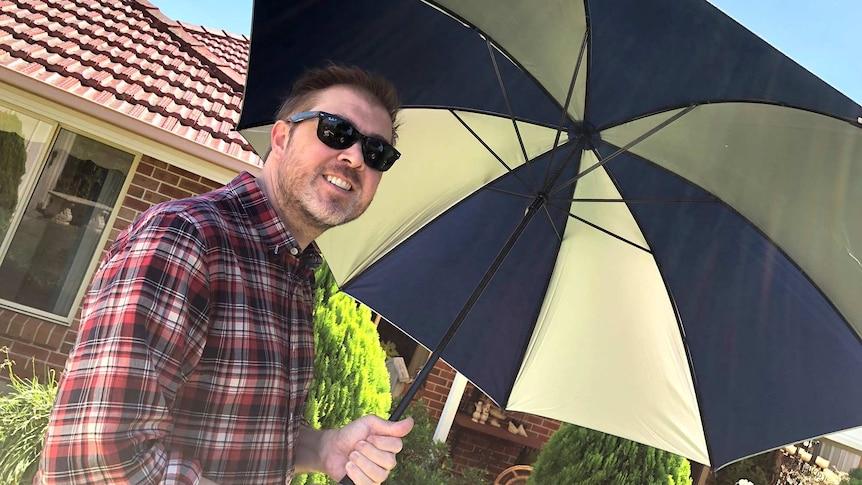 Damien MacRae holds an umbrella.