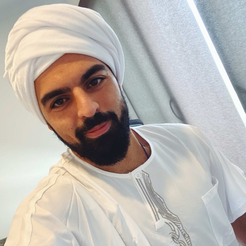 Ramtin poses for a selfie wearing a traditional Middle Eastern outfit.