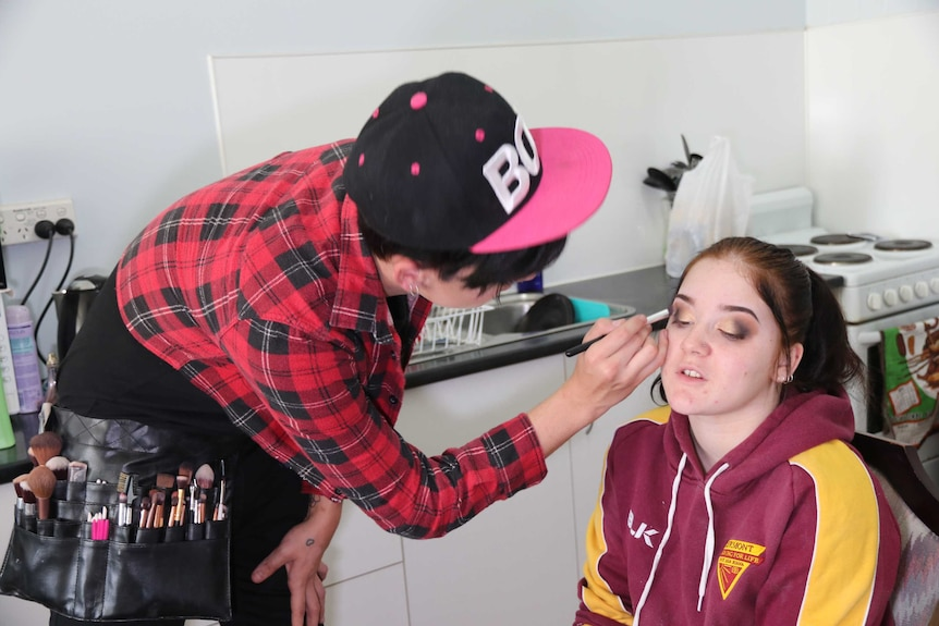 A makeup artist does eyeshadow on a client