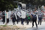 Riot police with shields charge towards a crowd of protesters.