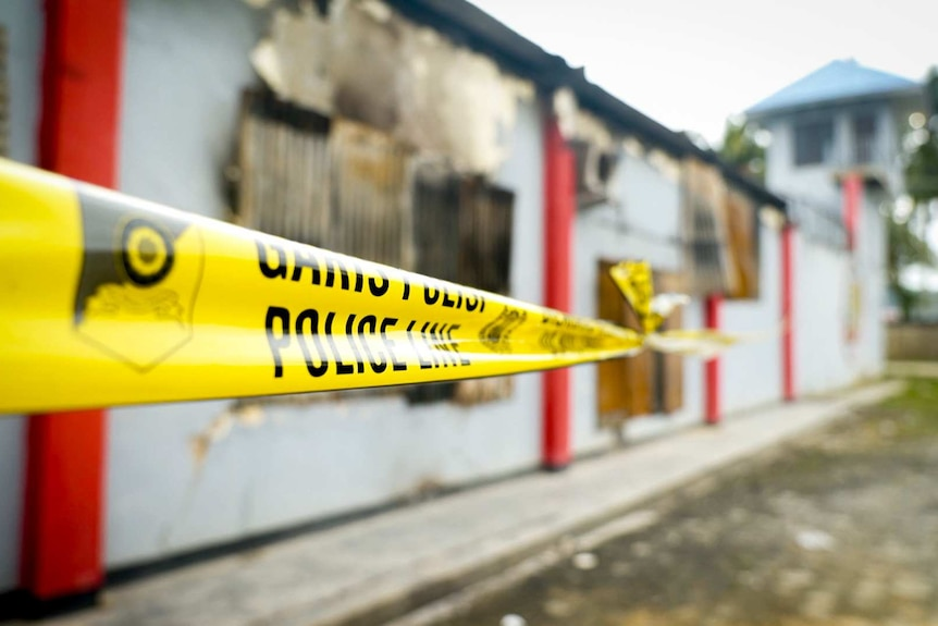 Police tape surrounds a fire-damaged building West Papuan jail where prisoners escaped during protests.