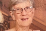 A elderly woman with short grey hair and small round glasses, wearing a pink top, smiling.