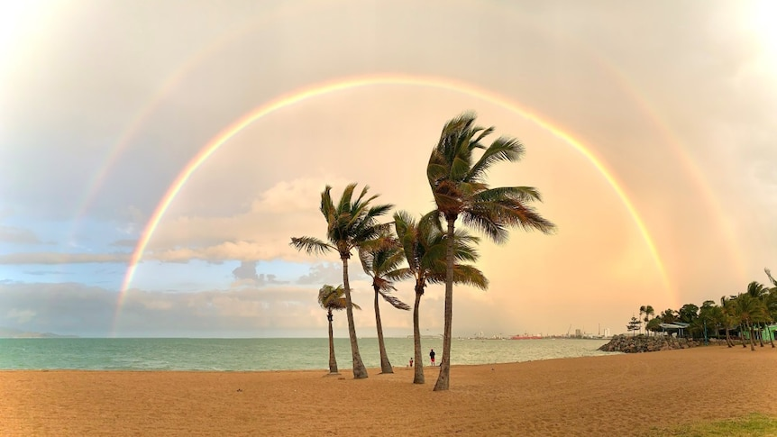 A double rainbow stretches over the sand and palm trees at the beach known as The Strand in Townsville.
