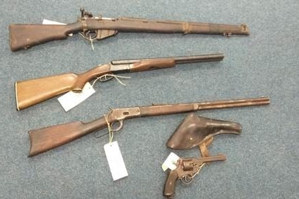 Four very old guns lying on a grey floor.