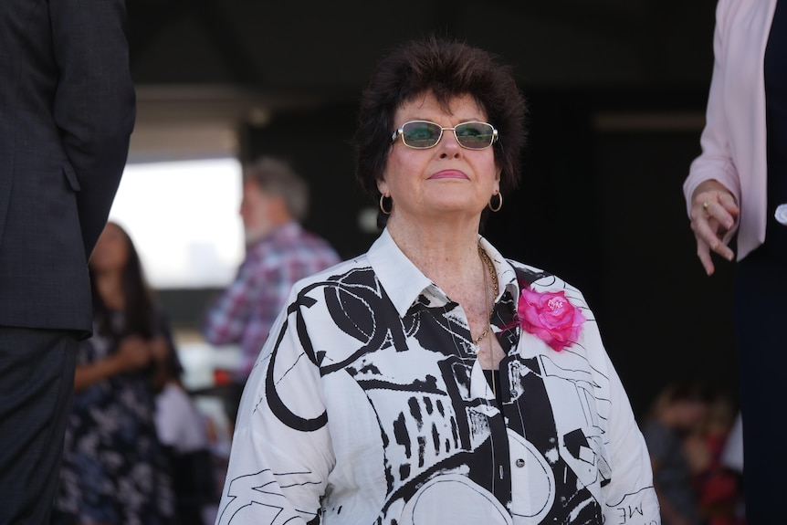 A woman standing wearing dark sunglasses and a patterned shirt
