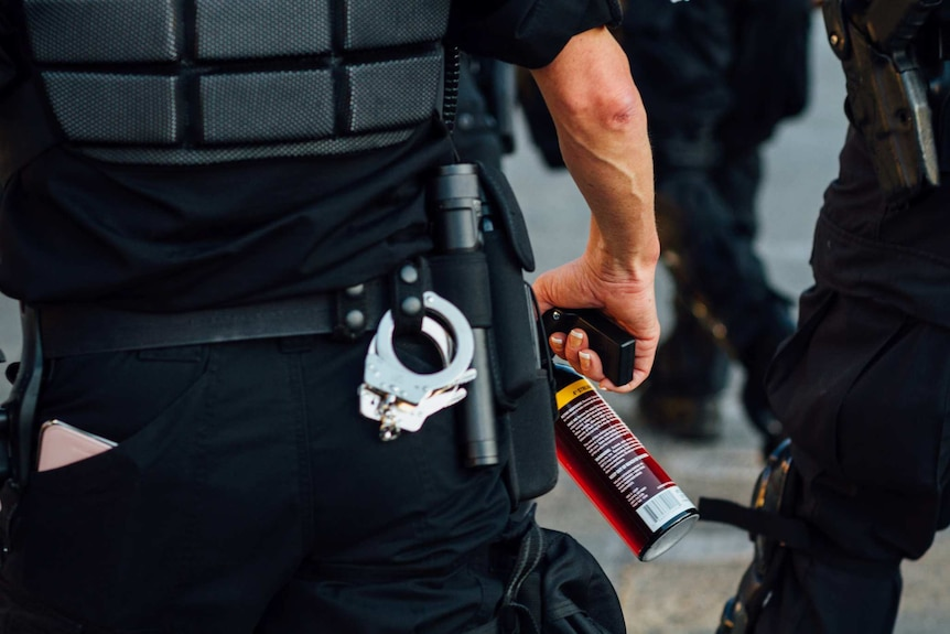 A police officer holds a can of pepper spray at a protest in Seattle in 2016.