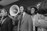 A black and white photo of a man in suit with a megaphone.