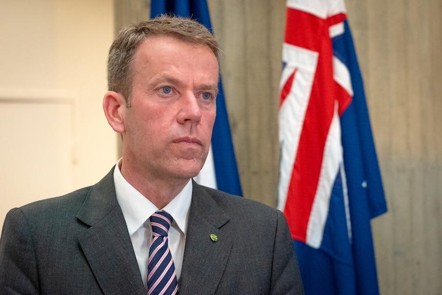 Un hombre con un traje gris se para frente a la bandera australiana.