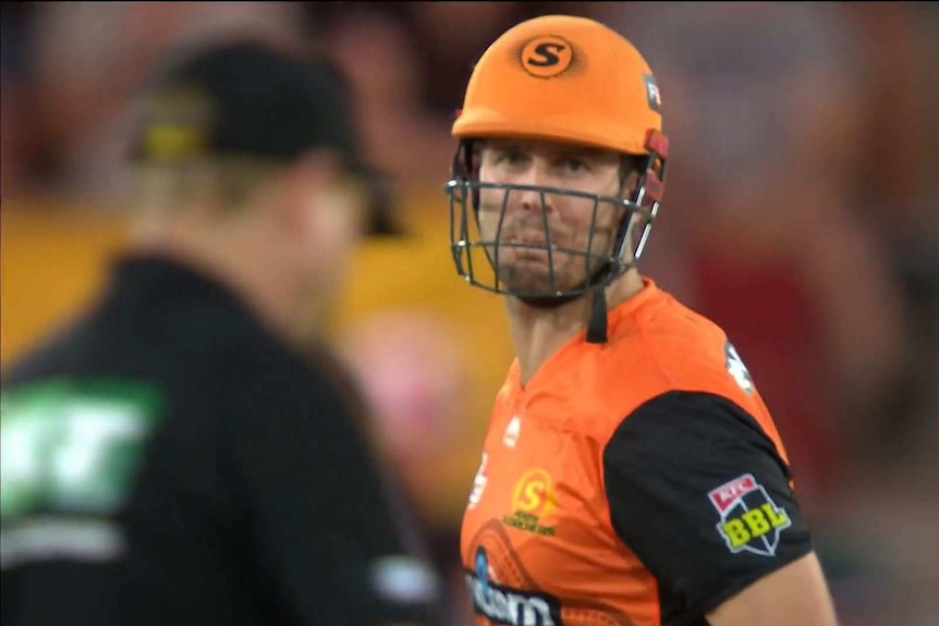 Perth Scorchers batsman Mitch Marsh purses his lips in anger as a BBL umpire walks past in the foreground.
