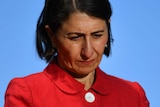 Gladys Berejiklian wears a red jacket and looks down towards the floor at a press conference