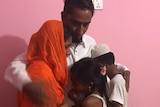 Eman Hossen hugging his family.