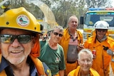 John Foster takes selfie photo of Woodgate firefighters all aged over 70, in uniform with fire trucks in the background.