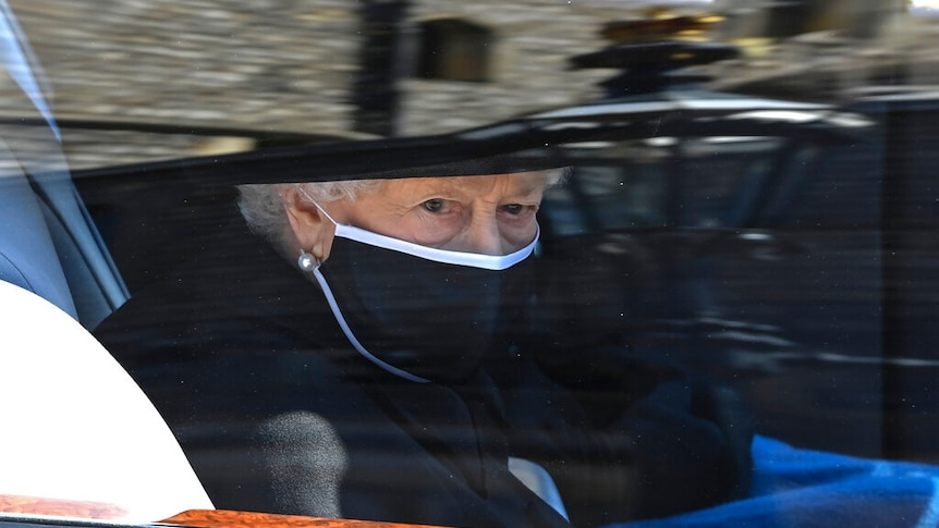 You view a closeup of the Queen wearing a black face mask and hat through the window of a car.
