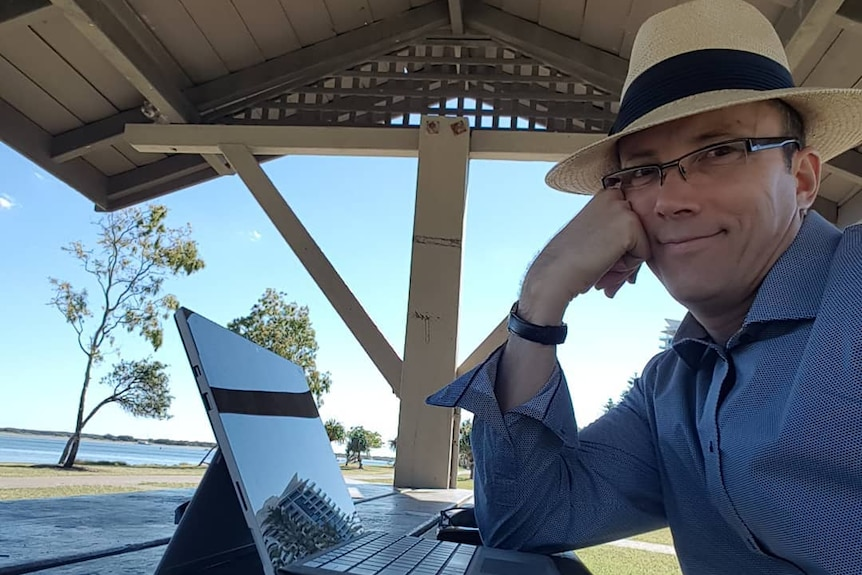 man in hat sitting in front of computer