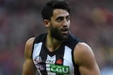 Alex Fasolo holds the football while playing against Essendon at the MCG.