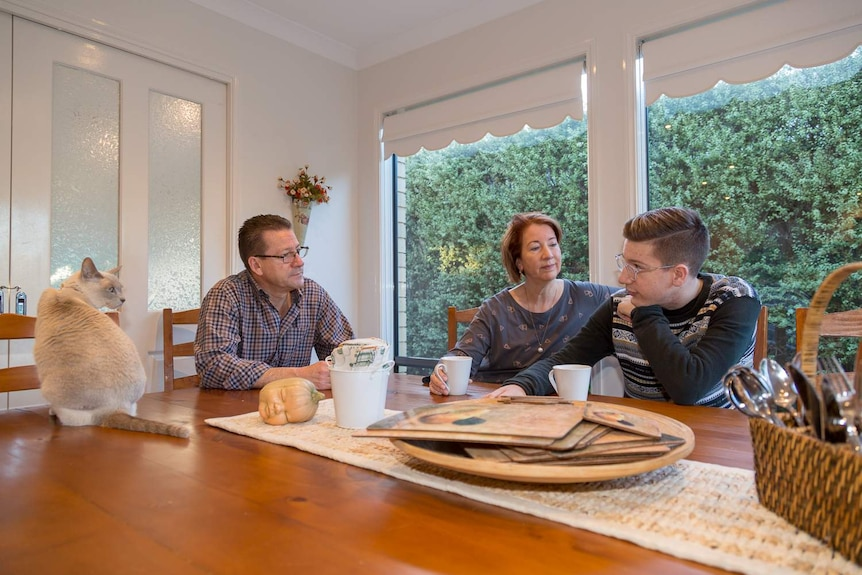 Jonah and his parents sit around their dining room table with coffee cups, talking.